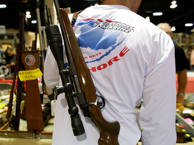A gun buyer carries a Browning Able rifle on his back while shopping at a gun show hosted by Florida Gun Shows, Saturday, Jan. 9, 2016, in Miami. Schlesinger purchased an Uzi and a Smith & Wesson 38. (AP Photo/Lynne Sladky)
