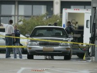 The car of an unidentified man who was shot while he pumped gas in Massaponax, Virginia, sits 11 October, 2002, as authorities examine the crime scene. Police launched a manhunt after another fatal shooting in the gas station near Washington, heightening public fears after seven killings by a sniper in …