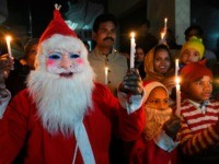 Christian devotees dressed as Santa Claus hold candles as they take part in a procession ahead of Christmas celebrations in Amritsar on December 21, 2019. (Photo by NARINDER NANU / AFP) (Photo by NARINDER NANU/AFP via Getty Images)