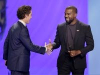Kanye West, right, shakes hands with senior pastor Joel Osteen during a service at Lakewood Church, Sunday, Nov. 17, 2019, in Houston. (AP Photo/Michael Wyke)