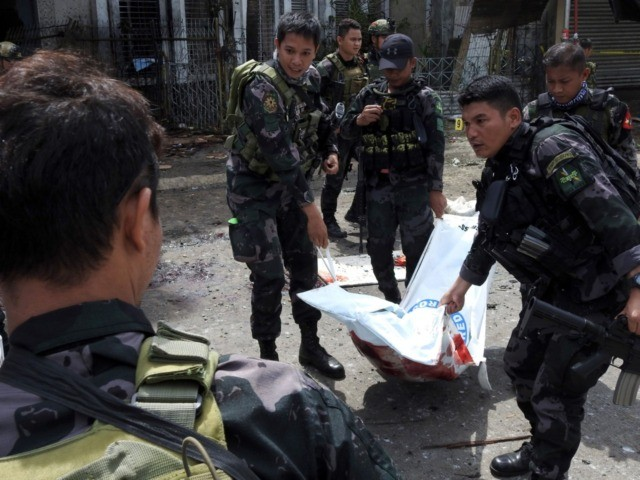 Philippine security personnel carry a body bag containing the remains of a blast victim after two bombs exploded at a church in Jolo, Sulu province on the southern island of Mindanao, on January 27, 2019. - At least 18 people were killed when two bombs hit a church on a …