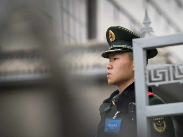 A paramilitary policeman stands guard outside a hotel where Guangdong delegation holds a meeting during the National People's Congress, China's legislature, in Beijing on March 6, 2018. President Xi Jinping's bid to rule for life has stunned many people in China. It left retired state-owned newspaper editor Li Datong cursing …