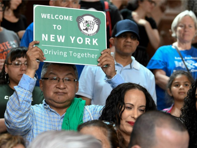 In this June 17, 2019 file photo, a protester holds a sign as members of the state Assembly speak in favor of legislation of the Green Light Bill, granting undocumented immigrant driver's licenses during a rally at the state Capitol, in Albany, N.Y. The bill passed making New York the …
