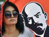 A Russian Communists' supporter stands by a flag picturing Vladimir Lenin, the founder of the Union of Soviet Socialist Republics (USSR), during a rally in downtown Moscow on August 22, 2016, to mark the symbolic 25th anniversary of the August 1991 putsch. On August 19, 1991, a group of security …