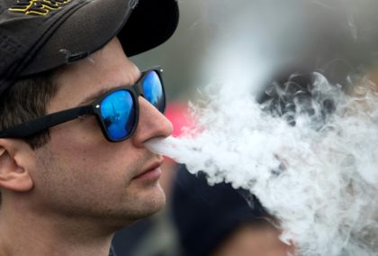 A demonstrator vapes during a rally outside of the White House to protest a ban on flavored vaping products in November 2019
