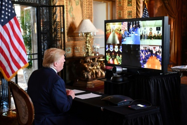 President Donald Trump makes a video call to deployed members of the US military from his Mar-a-Lago estate in Florida on December 24, 2019