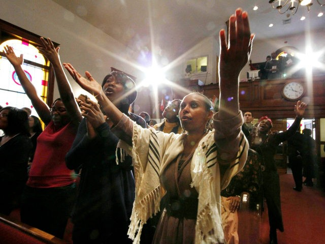 In this Feb. 27, 2011 photo, Salome Desta of Ethiopia and other members of the congregation worship during a church service at Pentacostal Tabernacle in Cambridge, Mass. The small historic black church, sitting between MIT and Harvard, has attracted students from Asia, Africa, Europe and Latin America to rejuvenate a …
