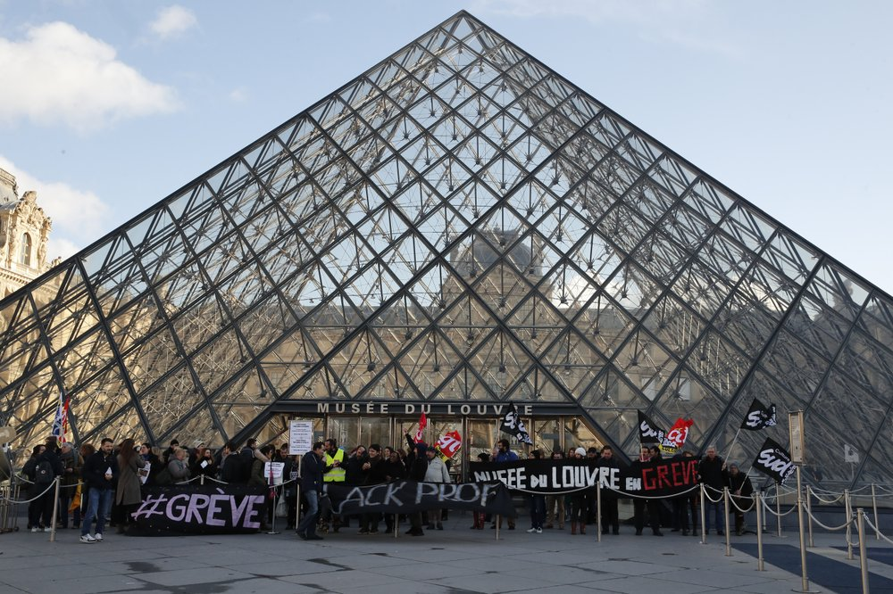 Striking employees hold banners outside the Louvre museum Friday, Jan. 17, 2020 in Paris. Paris' Louvre museum was closed Friday as dozens of protesters blocked the entrance to denounce the French government's plans to overhaul the pension system. (AP Photo/Francois Mori)