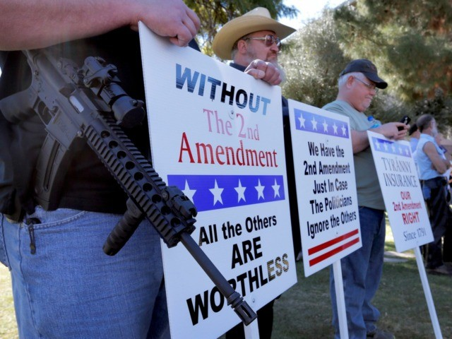 Gun rights supporters stand outside the Capitol Sat, Jan. 19, 2013 in Phoenix during a Guns Across America rally. The nationwide rally was in support of the 2nd Amendment and called for no new gun laws. (AP Photo/Matt York)