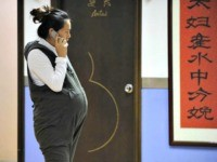 A pregnant woman speaks on the phone in Beijing Getty