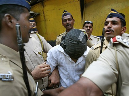 Police officers escort one of the four convicts in the gang rape of a photojournalist outside a prison to be taken to a court in Mumbai, India, Wednesday, March 26, 2014. An Indian court convicted the four last week for raping a photojournalist inside an abandoned textile mill in the …