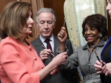 House Financial Services Committee Chairwoman Maxine Waters, D-Calif., holds up a pen presented to her by House Speaker Nancy Pelosi of Calif., after she signed the resolution to transmit the two articles of impeachment against President Donald Trump to the Senate for trial on Capitol Hill in Washington, Wednesday, Jan. …