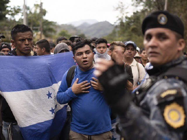 Honduran migrants walking in a group stop before Guatemalan police near Agua Caliente, Guatemala, Thursday, Jan. 16, 2020, on the border with Honduras. Less-organized migrants, tighter immigration control by Guatemalan authorities and the presence of U.S. advisers have reduced the likelihood that the hundreds of migrants who departed Honduras will …