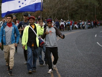 Honduran migrants walk north along a road in hopes of reaching the distant United States, one carrying a Honduran flag, as they leave Esquipulas, Guatemala, just after sunrise Friday, Jan. 17, 2020. The group departed San Pedro Sula on Jan. 15. (AP Photo/Moises Castillo)