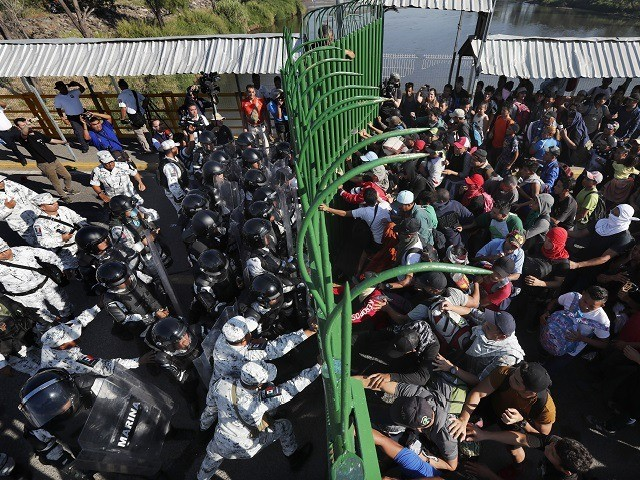 Migrants charge on the Mexican National Guardsmen at the border crossing between Guatemala and Mexico in Tecun Uman, Guatemala, Saturday, Jan. 18, 2020. More than a thousand Central American migrants surged onto the bridge spanning the Suchiate River, that marks the border between both countries, as Mexican security forces attempted …