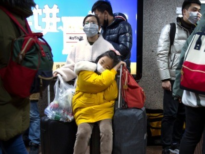 A girl wears a face mask as she sits on a suitcase at the Beijing West Railway Station in Beijing, Tuesday, Jan. 21, 2020. A fourth person has died in an outbreak of a new coronavirus in China, authorities said Tuesday, as more places stepped up medical screening of travelers …