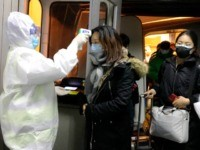 Health Officials in hazmat suits check body temperatures of passengers arriving from the city of Wuhan Wednesday, Jan. 22, 2020, at the airport in Beijing, China. Nearly two decades after the disastrously-handled SARS epidemic, China's more-open response to a new virus signals its growing confidence and a greater awareness of …