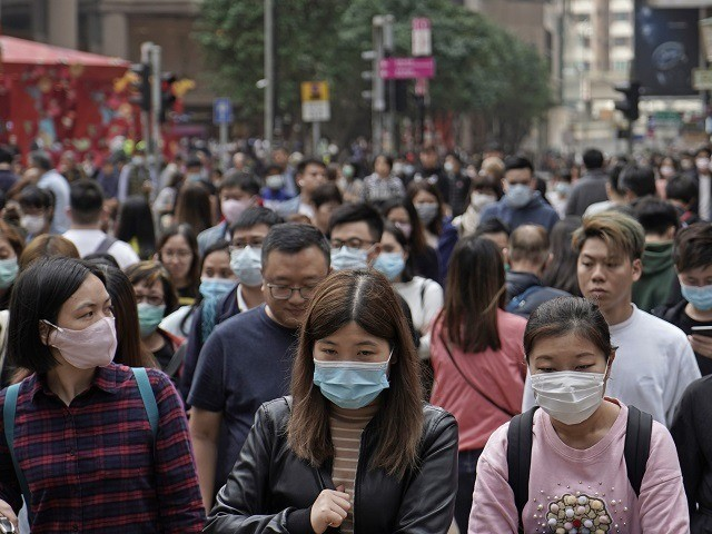 People wear masks on a street in Hong Kong, Friday, Jan. 24, 2020 to celebrate the Lunar New Year which marks the Year of the Rat in the Chinese zodiac. Cutting off access to entire cities with millions of residents to stop a new virus outbreak is a step few …
