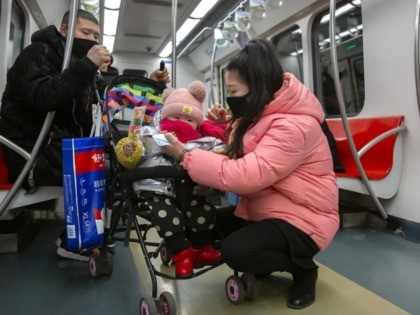 People wearing face masks attend to a child in a stroller as they ride a subway train in Beijing, Sunday, Jan. 26, 2020. The new virus accelerated its spread in China, and the U.S. Consulate in the epicenter of the outbreak, the central city of Wuhan, announced Sunday it will …
