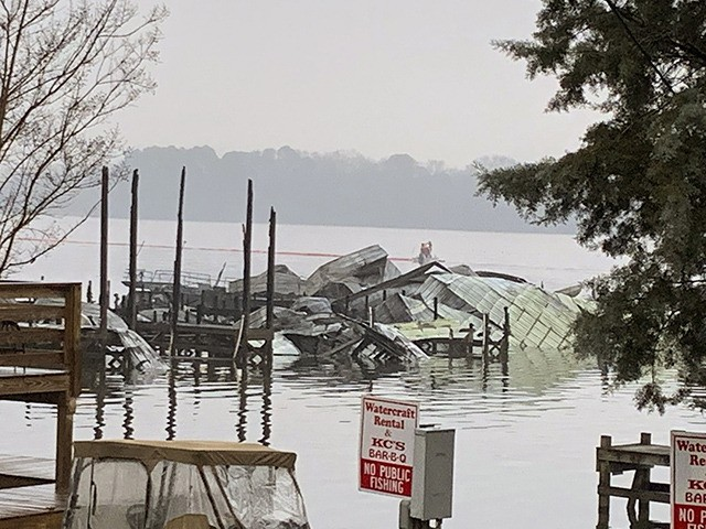 The remains of a dock where at least 35 vessels, many of them houseboats, were destroyed by fire early Monday, Jan. 27, 2020, in Scottsboro, Ala. Scottsboro Fire Chief Gene Necklaus is confirming fatalities in a massive fire at a boat dock. (Sierra Phillips/WAAY-TV via AP)