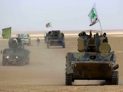 An infantry fighting vehicle (IFV) flying the flag of Asa'ib Ahl al-Haq, one of the units of the Hashed al-Shaabi (Popular Mobilisation units), advances with the Iraqi forces through Anbar province, 20 kilometres east of the city of Rawah in the western desert bordering Syria, on November 25, 2017, in …