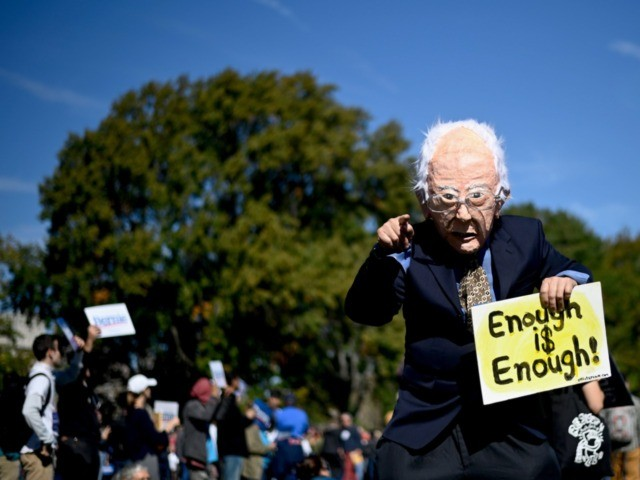 A supporter masked as 2020 Democratic presidential hopeful Bernie Sanders cheers while waiting for a campaign rally on October 19, 2019 in New York City. (Photo by Johannes EISELE / AFP) (Photo by JOHANNES EISELE/AFP via Getty Images)