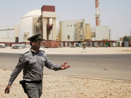 In this Aug. 21, 2010 file photo, an Iranian security officer directs media at the Bushehr nuclear power plant, with the reactor building seen in the background, just outside the southern city of Bushehr, Iran. State TV says the Guardian Council, Iran's constitutional watchdog, ratified a bill Wednesday, June 24, …