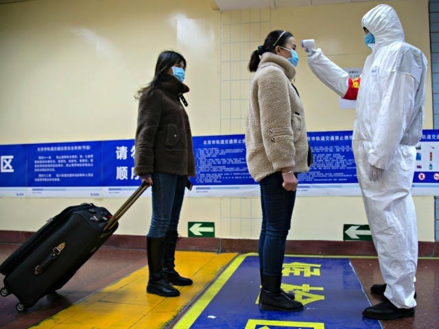 BEIJING, CHINA - JANUARY 26: A health worker checks the temperature of women entering the subway on January 26, 2020 in Beijing, China. The number of cases of coronavirus rose to 1,975 in mainland China on Sunday. Authorities tightened restrictions on travel and tourism this weekend after putting Wuhan, the …