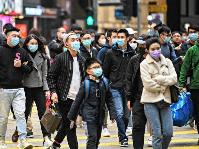 Pedestrians wearing face masks cross a road during a Lunar New Year of the Rat public holiday in Hong Kong on January 27, 2020, as a preventative measure following a coronavirus outbreak which began in the Chinese city of Wuhan. (Photo by Anthony WALLACE / AFP) (Photo by ANTHONY WALLACE/AFP …