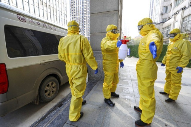 Funeral workers disinfect themselves after handling a virus victim in Wuhan in central China's Hubei Province, Thursday, Jan. 30, 2020. China counted 170 deaths from a new virus Thursday and more countries reported infections, including some spread locally, as foreign evacuees from China's worst-hit region returned home to medical observation …