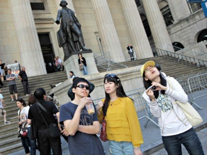 FILE - In this June 15, 2012, file photo, a group of tourists from China take in the sights of the New York Stock Exchange and Federal Hall National Memorial, in New York. With tens of millions of Chinese ordered to stay put and many others opting to avoid travel …