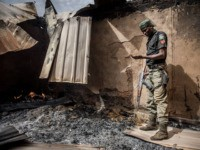 A Nigerian Police Officer patrols an area of destroyed and burned houses after a recent Fulani attack in the Adara farmers' village of Angwan Aku, Kaduna State, Nigeria on April 14, 2019. - The ongoing strife between Muslim herders and Christian farmers, which claimed nearly 2,000 lives in 2018 and …
