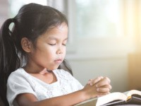 Girl closed her eyes and folded her hand in prayer on a Holy Bible