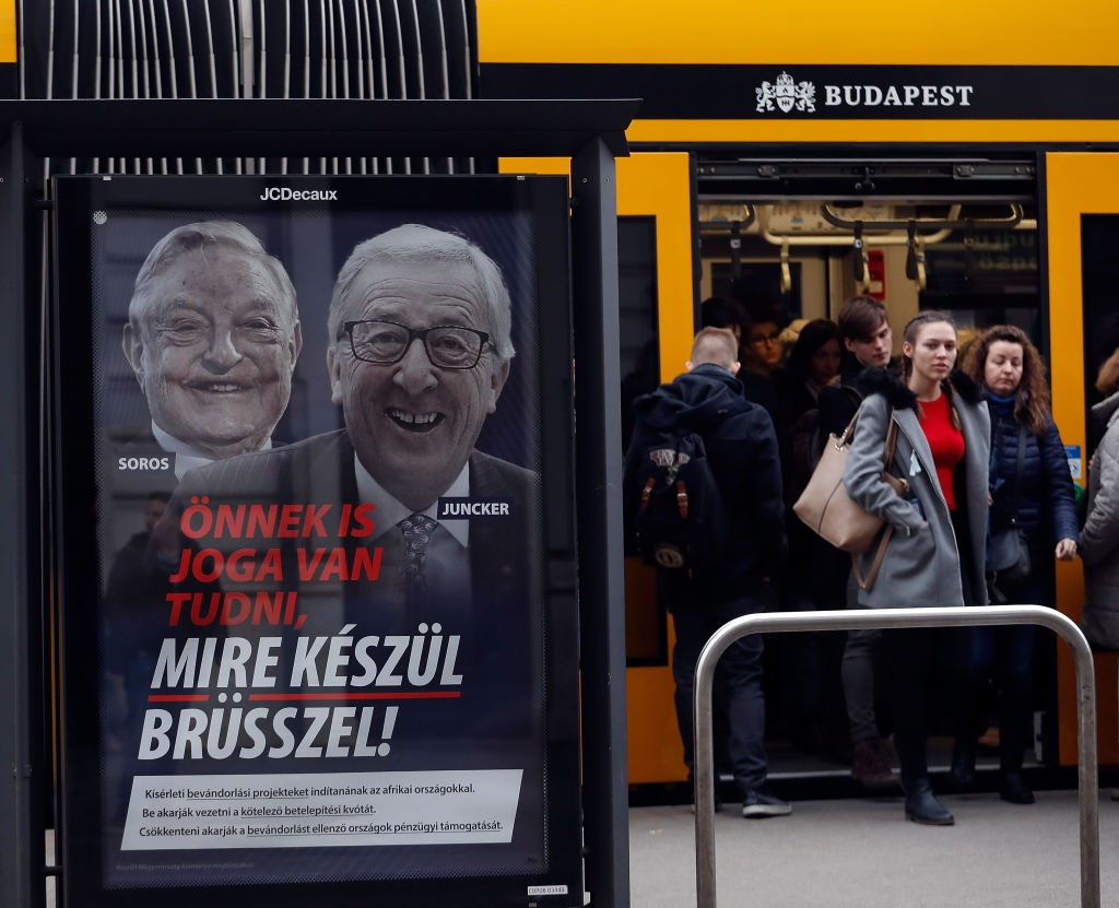 "BUDAPEST, HUNGARY - FEBRUARY 22:  People leave from the tram next to a billboard with portraits of European Commission chief Jean-Claude Juncker  and Hungarian-born US billioner George Soros and a slogan reading ""You too have a right to know what Brussels is preparing""on February 22, 2019 in Budapest, Hungary.Hungary launched a new anti-immigration media campaign prior the European parliamentary election.(Photo by Laszlo Balogh/Getty images)"