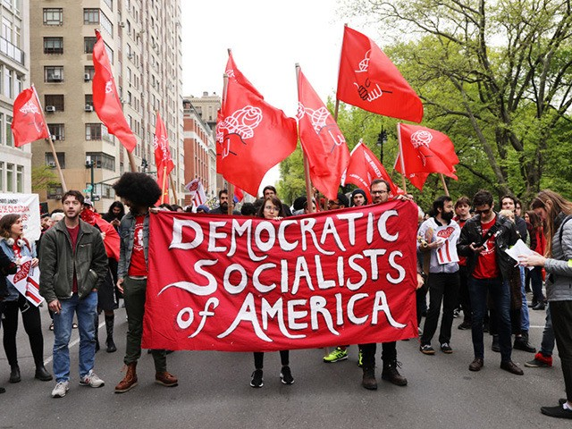 NEW YORK, NEW YORK - MAY 01: Members of the Democratic Socialists of America gather outside of a Trump owned building on May Day on May 01, 2019 in New York City. Around the country and the world people are marching and demonstrating for better working conditions, higher salaries, maternity …