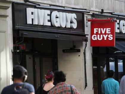 Pedestrians pass a branch of a Five Guys restaurant in London on August 23, 2019. (Photo by Isabel INFANTES / AFP) (Photo credit should read ISABEL INFANTES/AFP via Getty Images)