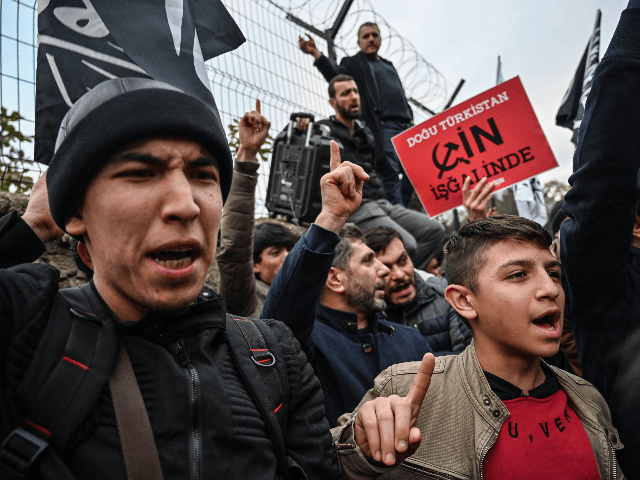 "Supporters of China's Muslim Uighur minority and Turkish islamists chant slogans as they hold a placard reading ""East Turkistan under occupation by China"" on December 13, 2019 during a demostration in front of China Consulate in Istanbul. - One million Uighurs and other mostly Muslim minorities, including ethnic Kazakhs, are …"