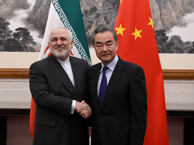 China's Foreign Minister Wang Yi (R) shakes hands with Iran's Foreign Minister Mohammad Javad Zarif during their meeting at the Diaoyutai State Guest House in Beijing on December 31, 2019. (Photo by Noel CELIS / POOL / AFP) (Photo by NOEL CELIS/POOL/AFP via Getty Images)