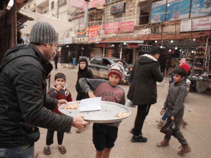 A Syrian man in the rebel-held town of Dana in the northwestern province of Idlib offers sweets to children to mark the killing on January 3, 2020 of Qasem Soleimani, a top Revolutionary Guards commander in Iran, seen by the rebels as a main supporter of the Syrian regime which …