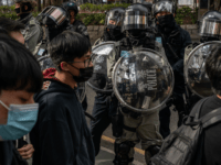 "Protesters march on a street as riot police stand guard during a rally against parallel traders in Sheung Shui district on January 5, 2020 in Hong Kong, China. Anti-government protesters in Hong Kong continue their demands for an independent inquiry into police brutality, the retraction of the word ""riot"" to …"