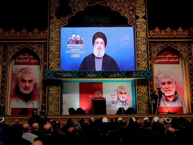 "Supporters of the the Shiite Hezbollah movement watch as the movement's leader Hasan Nasrallah delivers a speech on a screen, in the Lebanese capital Beirut's southern suburbs on January 5, 2020. - Nasrallah called on Iraq to free itself of the American ""occupation"" after top Iranian general Qasem Soleimani was …"