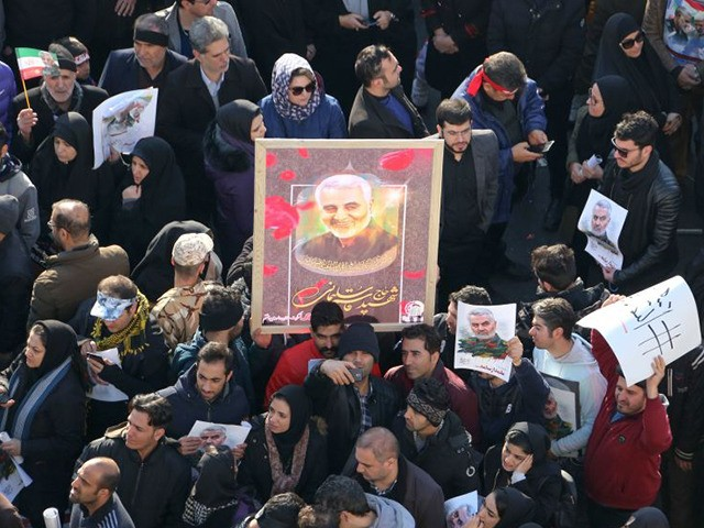 Iranian mourners lift a picture of slain military commander Qasem Soleimani during a funeral procession in the capital Tehran on January 6, 2020, for him as well as Iraqi paramilitary chief Abu Mahdi al-Muhandis and other victims of a US attack. - Downtown Tehran was brought to a standstill as …