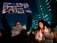 TOPSHOT - A woman holds a sign for one of the victims of Ukrainian Airlines flight 752 which crashed in Iran, during a vigil at Mel Lastman Square in Toronto, Ontario on January 9, 2020. - A Ukrainian airliner crashed shortly after take-off from Tehran on January 8 killing all …