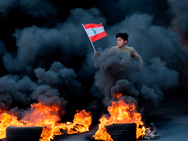 """A Lebanese youth runs with a national flag as smoke billows from burning tires during a demonstration in Jal el-Dib area on the northern outskirts of the Lebanese capital Beirut on January 14, 2020. - Lebanese protesters resumed blocking major highways in what they said would be a """"week of …"""