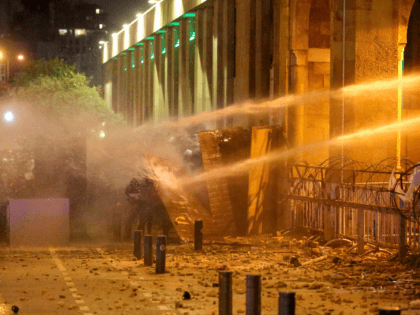 Lebanese protesters take cover as riot police spray them with water from behind a barricaded road leading to parliament in central Beirut on January 19, 2020 amid ongoing anti-government demonstrations. - Lebanese anti-riot police fired rubber bullets and water cannons at stone-throwing demonstrators in the Lebanese capital today, as hundreds …