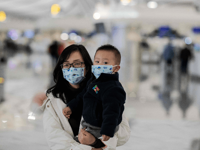 woman and a child wearing protective masks walk toward check-in counters at Daxing international airport in Beijing on January 21, 2020. - The death toll from a new China virus that is transmissible between humans rose to six, the mayor of Wuhan said in an interview with state broadcaster CCTV …