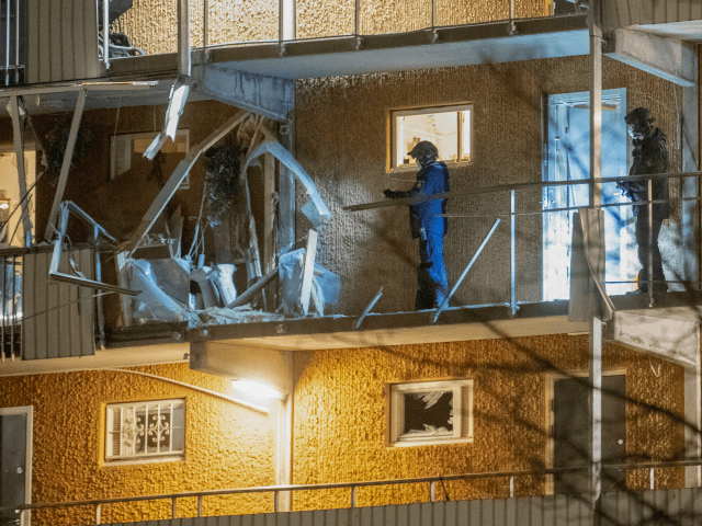 Police search a residential building that was hit by an explosion injuring one person in Husby outside of Stockholm, on January 21, 2020, where two blasts occurred within some minutes and a few hundred metres away one from each other. (Photo by Fredrik SANDBERG / TT News Agency / AFP) …