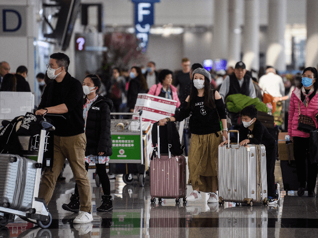 Passengers wear face masks at Hong Kong's international airport on January 22, 2020, after China recently confirmed human-to-human transmission in the outbreak of the new SARS-like virus. - A new virus that has killed nine people, infected hundreds and already reached the United States could mutate and spread, China warned …