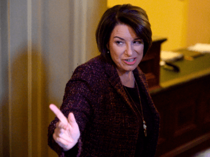 US Senator and presidential candidate Amy Klobuchar (D-MN) (R) gestures during a recess in the Senate impeachment trial of US President Donald Trump at the US Capitol in Washington, DC, January 22, 2020. - In a somber and hushed Senate chamber, Democrats began presenting their opening arguments in the impeachment …
