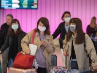 TOPSHOT - Passengers wear protective masks to protect against the spread of the Coronavirus as they arrive at the Los Angeles International Airport, California, on January 22, 2020. - A new virus that has killed nine people, infected hundreds and has already reached the US could mutate and spread, China …